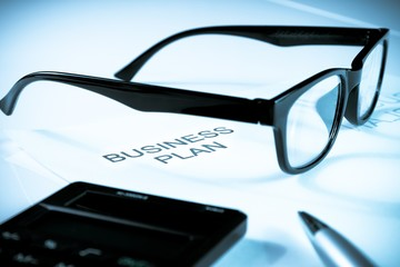 business plan words near glasses, pen and calculator