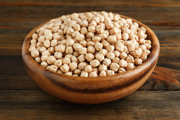 Chickpeas in a wooden bowl on wood closeup