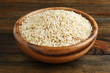 Unpolished rice in a wooden bowl on wood closeup