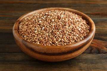 Buckwheat in a wooden bowl on wood closeup