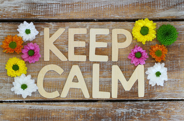 Keep calm written with wooden letters and santini flowers