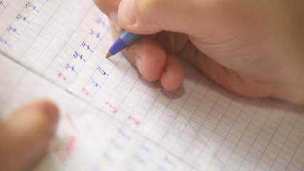 Little pupil write digits in square grid notebook