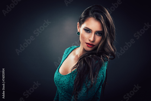 Beautiful young woman in a green dress with curly long hair