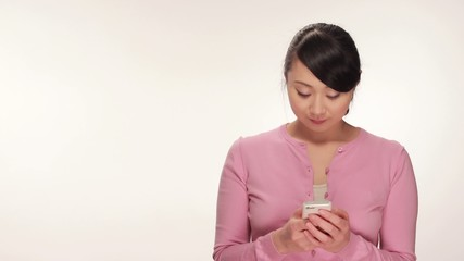 Young Asian woman texting on cellphone