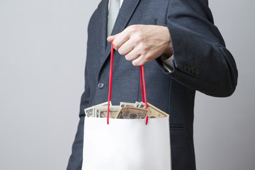 Businessman with package full of money in the hands of