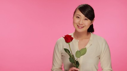 Young Asian woman holding red rose flower