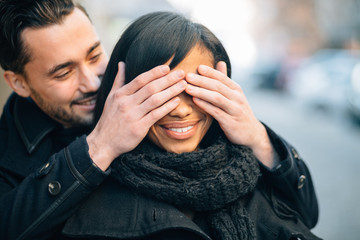 Young man in love surprising his girlfriend on street