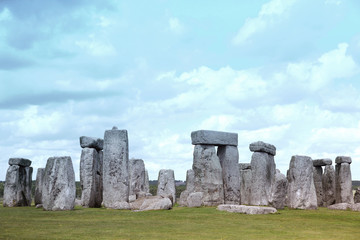Stonehenge historic site on green grass under blue sky. Stonehen