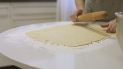 A woman prepares dough for cookies