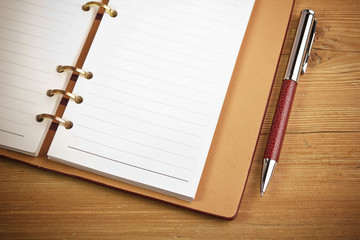 notepad with pen lying on the wooden table