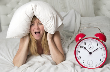 Woman in bed with head under pillow and a ringing alarm clock