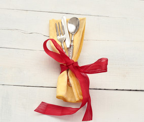 elegant  vintage silverware inside yallow napkin with red bow