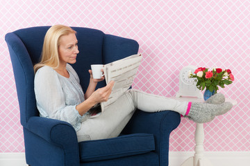 woman relaxing in chair reading newspapers