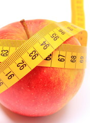 Fresh apple and tape measure on white background
