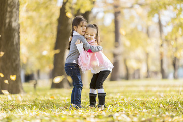 Little girls in the autumn park