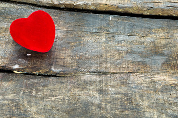 Red Valentine heart on old rustic wooden background