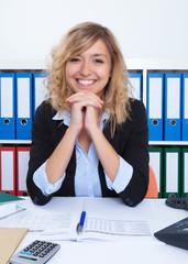 Sympathische Frau mit blonden Locken im Büro
