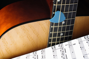 Acoustic guitar and sheet music close up