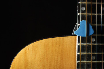 Close up of beautiful guitar body and blue guitar pick