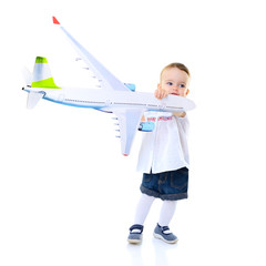 Cute little girl stewardess playing with airplane, studio over w