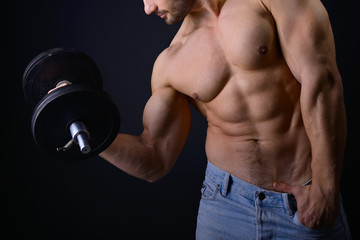 strong athletic man with perfect body posing with dumbbells on b