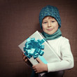 Cute happy christmas little boy with present box over vintage ca