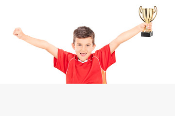 Cheerful junior holding a trophy behind a panel