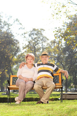 Mature couple sitting on bench in a park