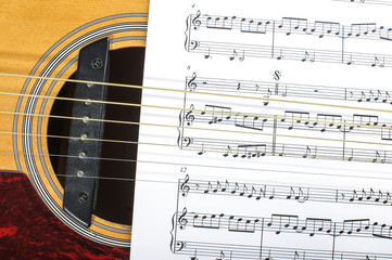 Acoustic guitar sound hole and sheet music notes paper