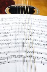Sheet music notes under six guitar strings