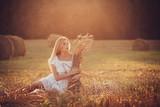 Happy gentle girl relaxing in a field on sunset