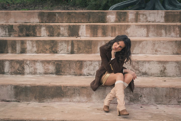 Beautiful young woman sitting on concrete steps