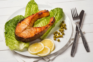 Fried trout with a piece of lettuce, lemon and green peas