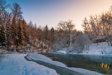 Winter frosty landscape at sunset in the forest with a river