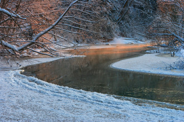 Winter landscape in the forest with the river in frosty sunset