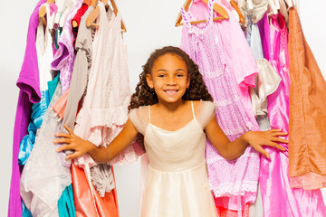 Small African girl standing between hangers