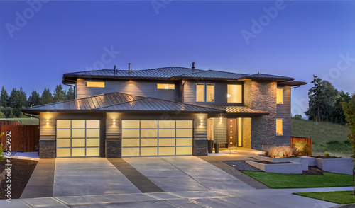 Front elevation of luxury home in evening - 76029302