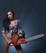 Tempting young woman posing with chainsaw