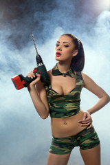 Concept photo. Beddable woman armed with drill