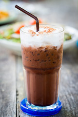 Iced milk chocolate with straw on wood table