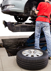 Mechanic repairing the wheel area of vehicle