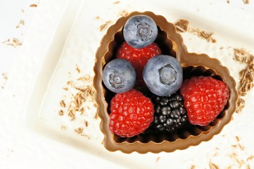 Heart shaped chocolate cup with berries on white plate