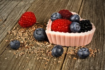 Pink heart shaped chocolate dessert cup with berries on wood