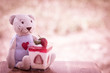 Teddy bear doll with strawberry cheescake  on meadow background