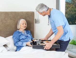 Nurse Serving Breakfast To Senior Woman On Bed
