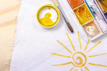 artist's brush on a background painted yellow sun