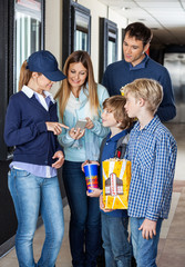 Family Showing Movie Tickets To Worker On Smartphone