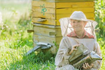 Teenage beekeeper with painted wooden beehives
