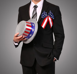 Man in suit holding Hat with American Flag over gray background