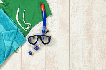 Swimming Trunks, Towel And Snorkeling Mask On Floorboard